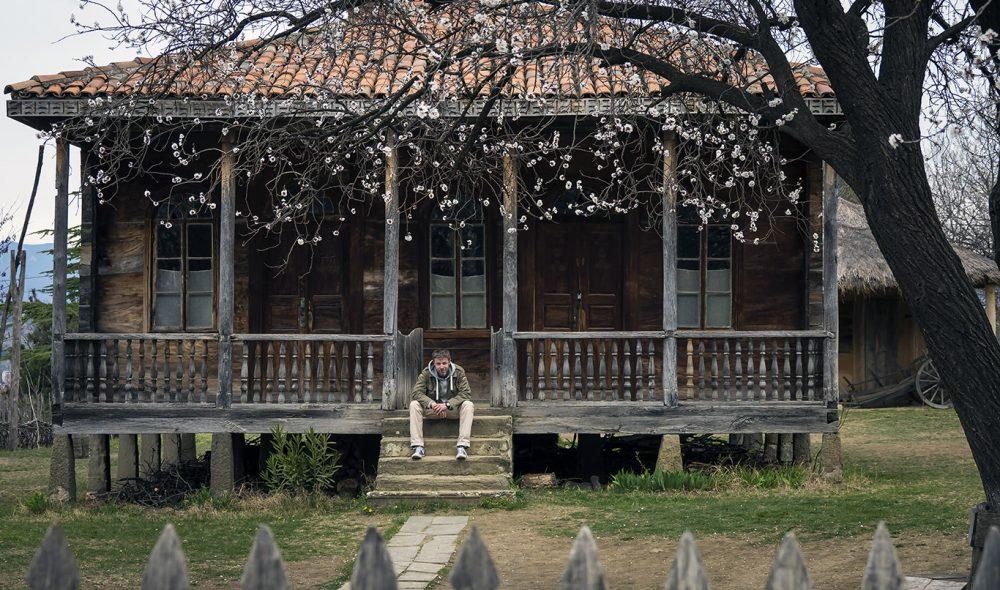 PÅ MUSEUM: Den unge guiden Tsotne Japaridze utenfor et av husene i Tbilisis etnografiske utendørsmuseum, som langt på vei er modellert etter Maihaugen på Lillehammer.
